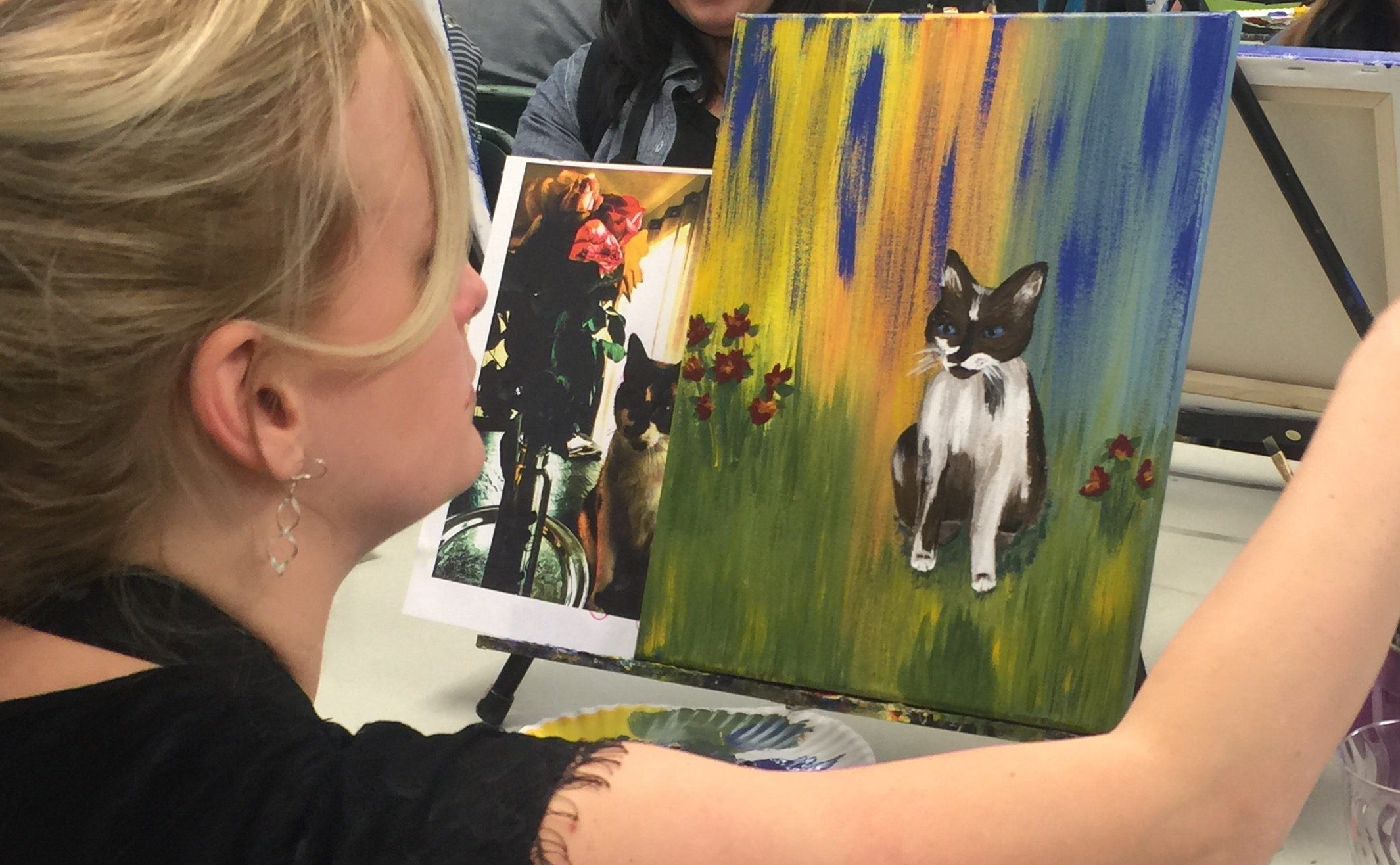 An artist paints an image of their cat.